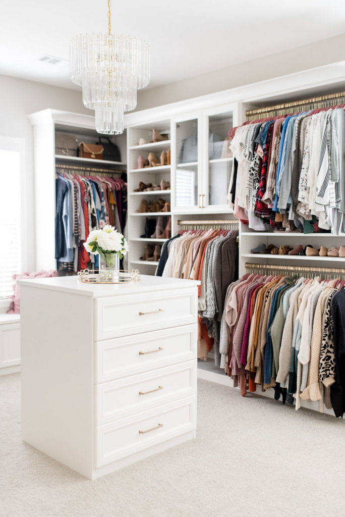 custom walk in closet with white center console of drawers and chandelier