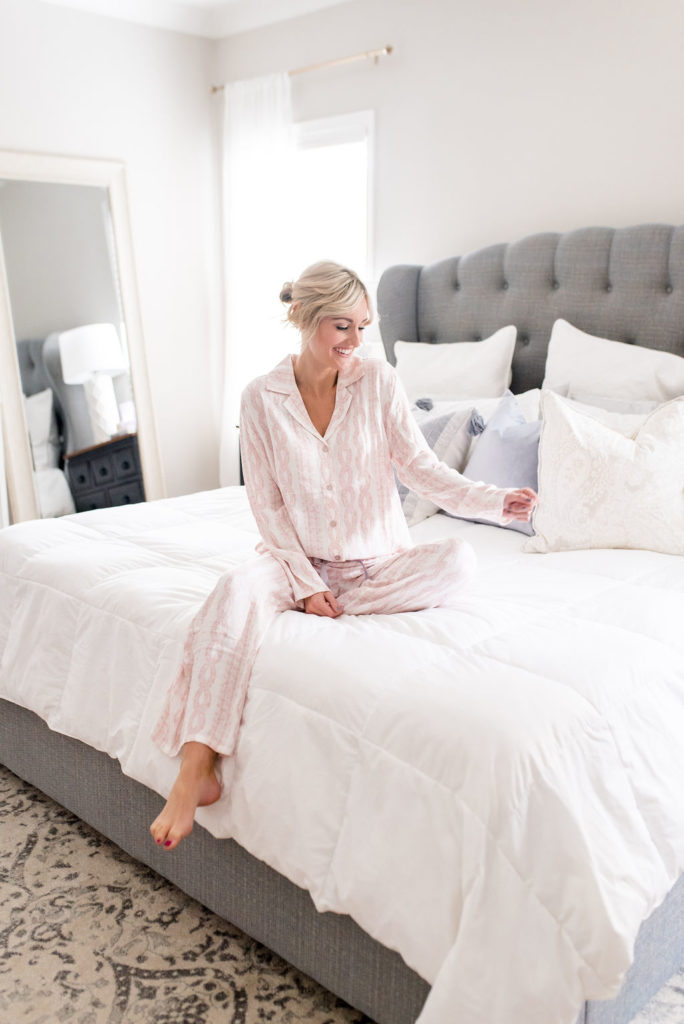 woman in bedroom wearing pink soma intimates long sleeve top and pants matching pajama set