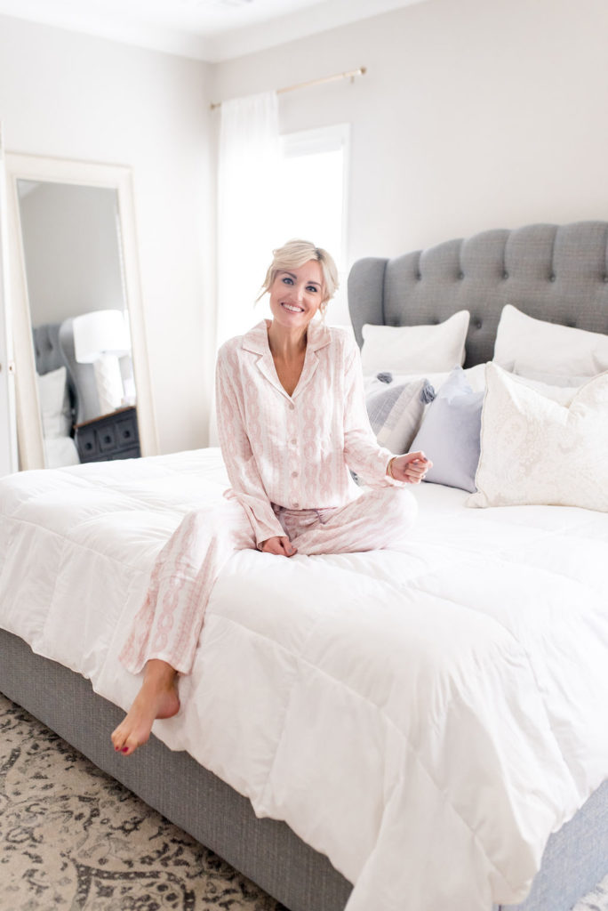 woman in bedroom wearing cozy pink soma intimates long sleeve top and pants matching pajama set
