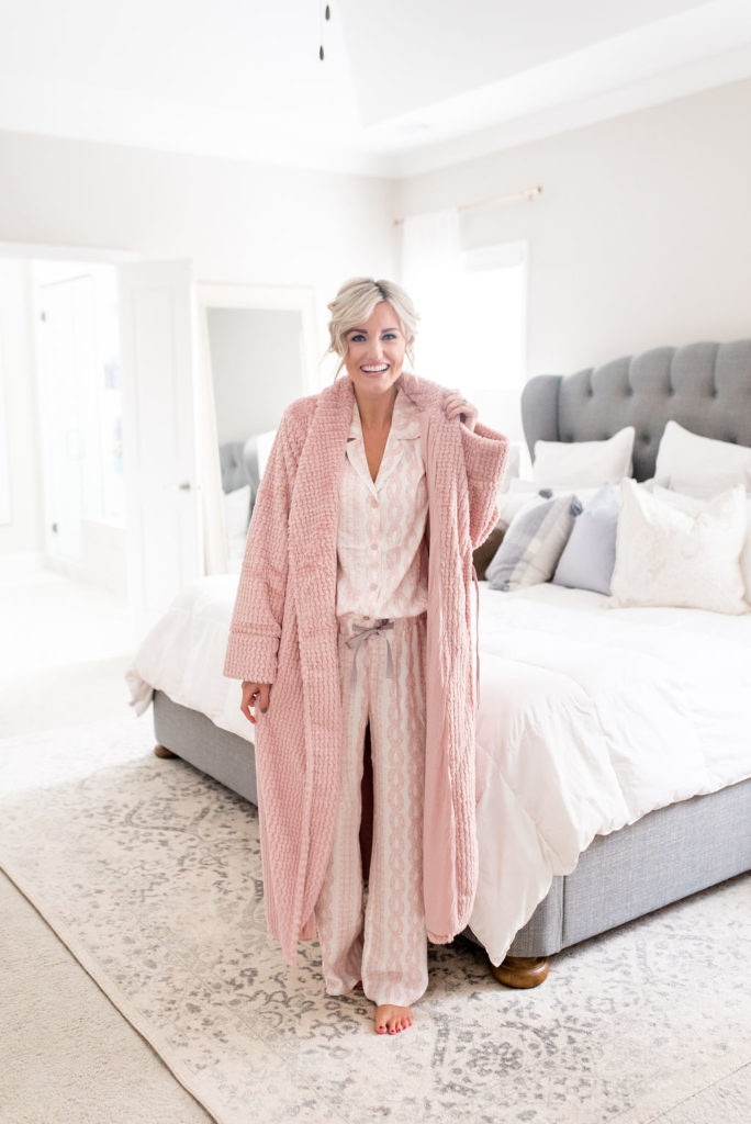 woman standing in bedroom wearing woman in bedroom wearing cozy pink soma intimates long sleeve top and pants matching pajama set with pink bath robe