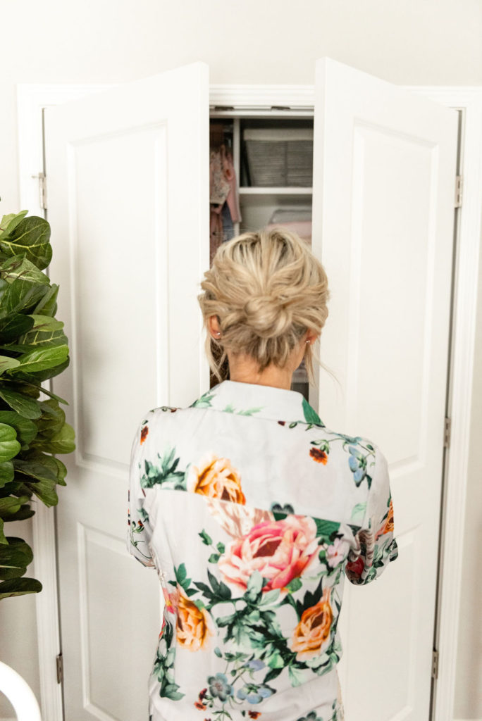 blond woman opening nursery closet