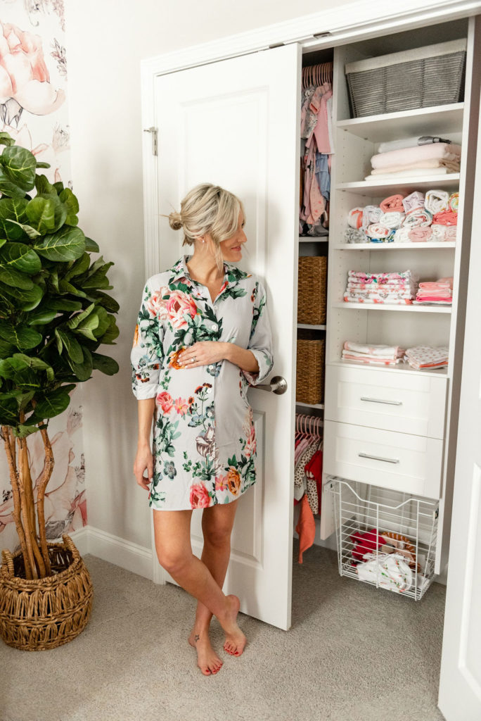 pregnant woman with organized nursery closet