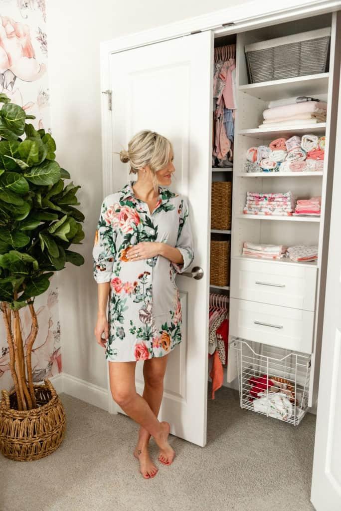pregnant woman with organized nursery closet