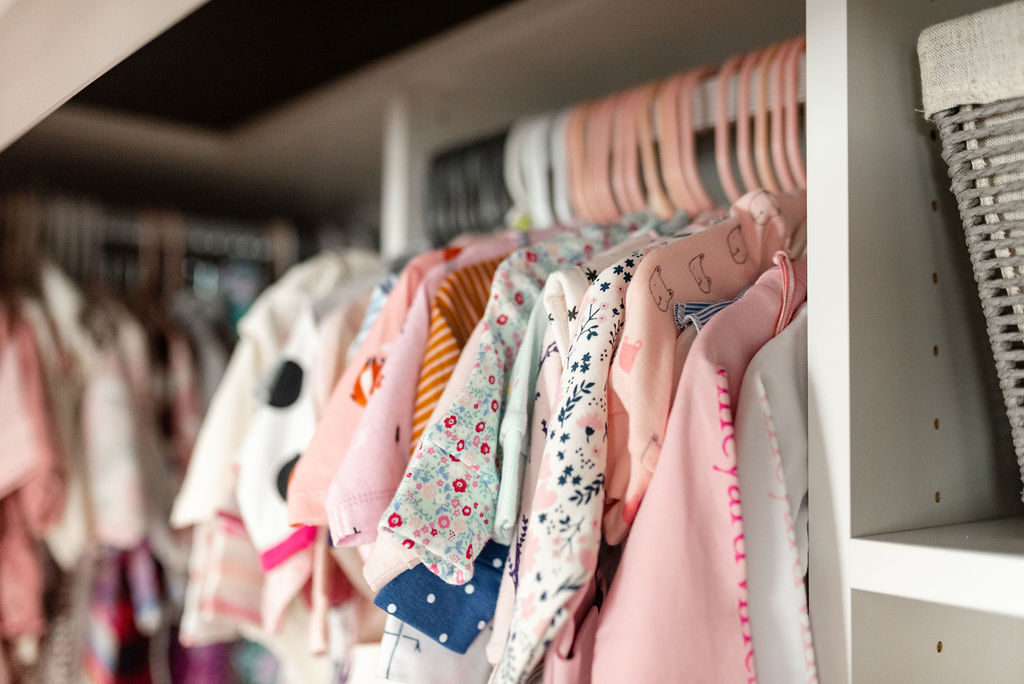 baby clothes hanging in nursery closet