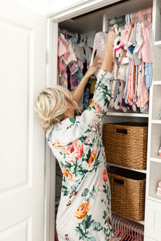 blond woman hanging up baby clothes in california closet baby nursery