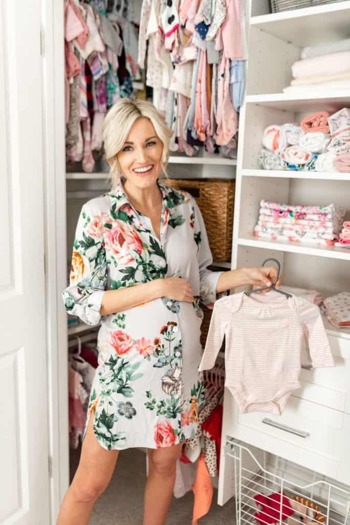 pregnant woman smiling in new california closet baby nursery closet