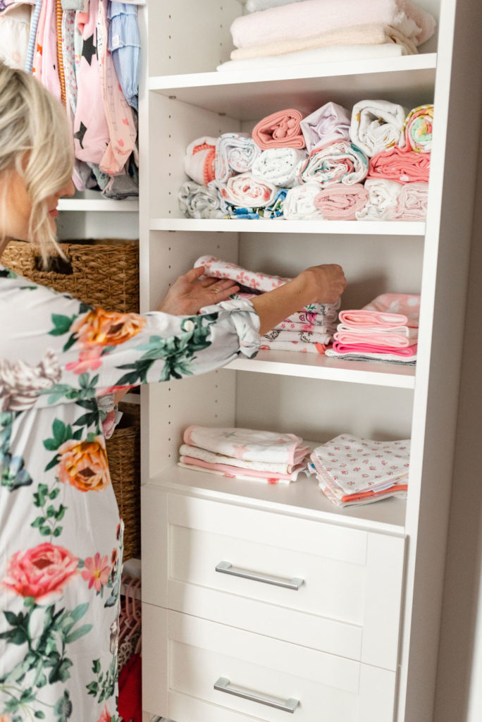 folding and stacking baby clothes in california baby nursery closet