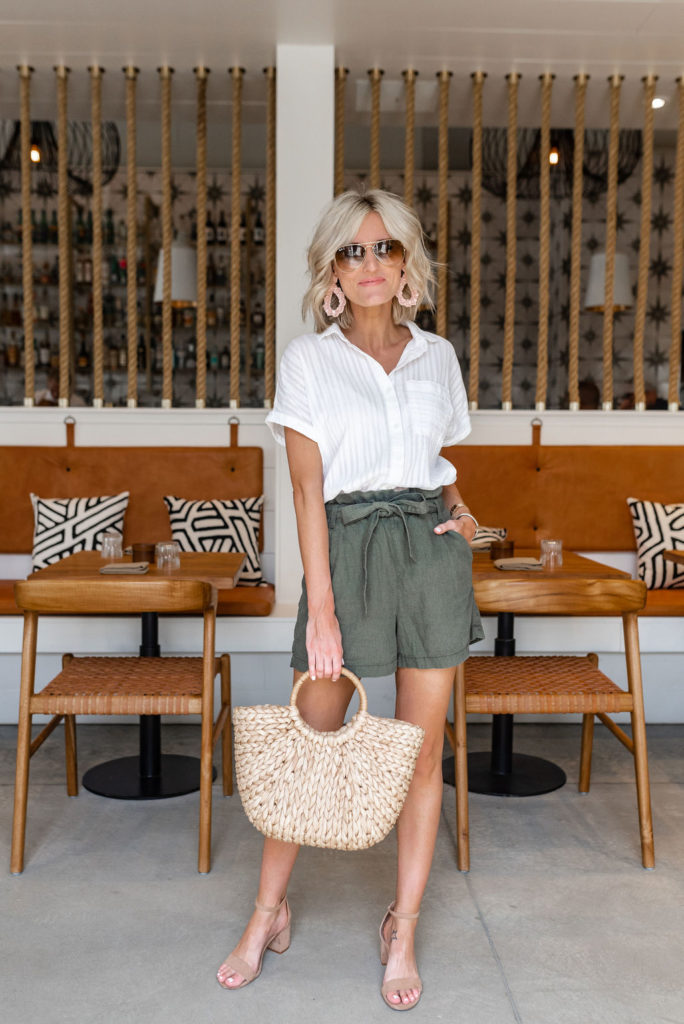 fashion blogger wearing olive green paper bag shorts with white button down short sleeve blouse carrying straw handbag from JCPenney