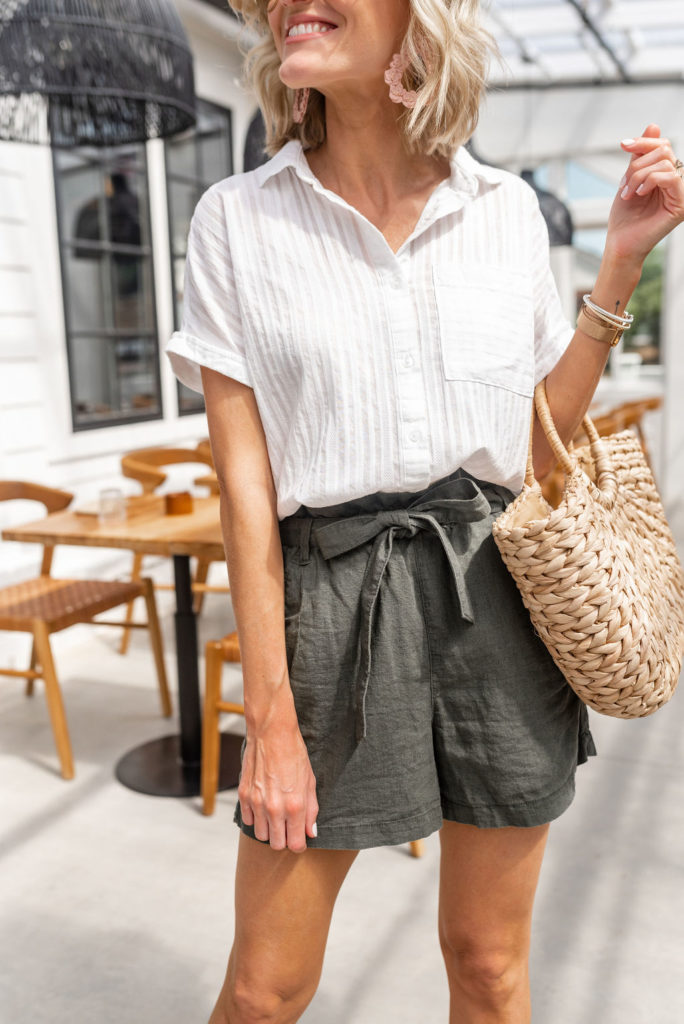 olive green paper bag shorts from JCpenney styled with white stripe short sleeve button down and straw handbag for summer